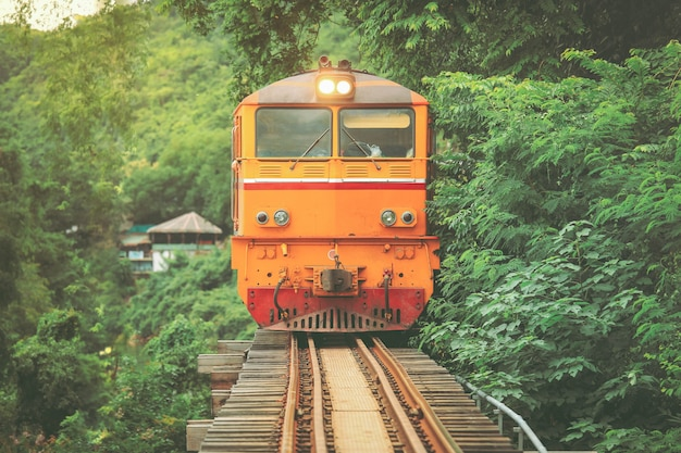 The train on the bridge over the river kwai in kanchanaburi, thailand. this bridge is famous for its history in second world war.