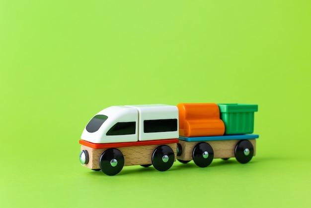 어린이 장난감, 취학 전 어린이 게임을 훈련하십시오. 기관차 및 마차, 녹색 배경 측면 보기에 다채로운 나무 블록 건설