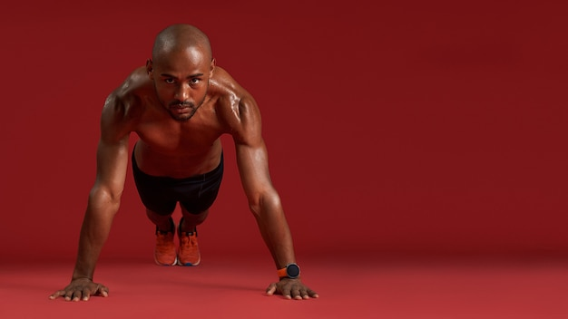 Train harder full length of strong african man in sports clothing doing pushups isolated over