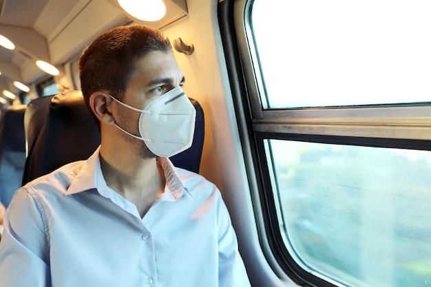 Пассажир поезда с защитной маской, глядя в окно