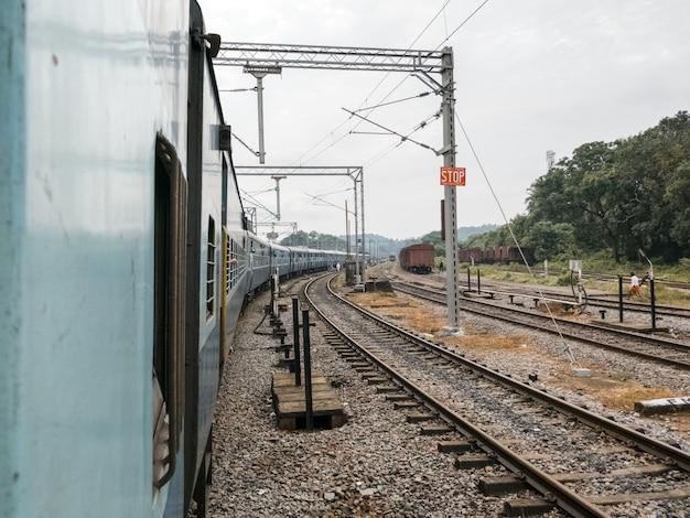 Treno che passa in una stazione ferroviaria su uno sfondo di ferrovia