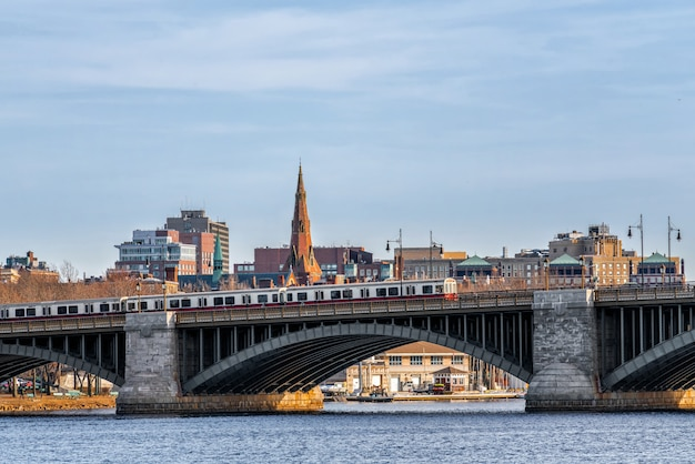 Train running over the longfellow bridge the charles river at the evening time, usa downtown skyline