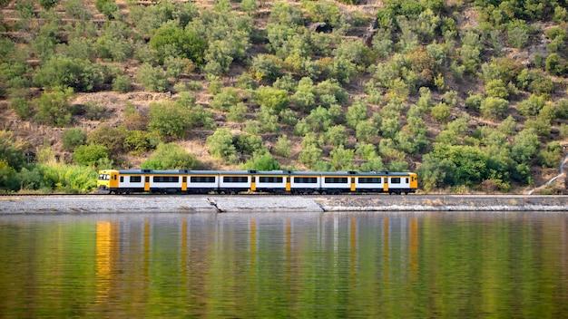 川と平行に走り、水に映る列車