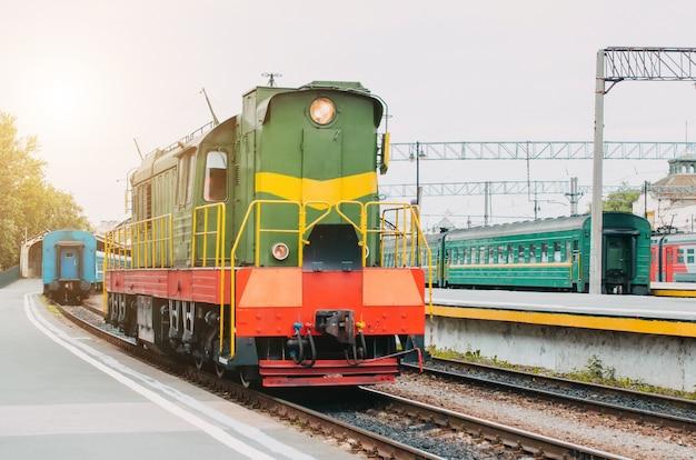 Поезд, маневровый локомотив на пассажирской платформе.