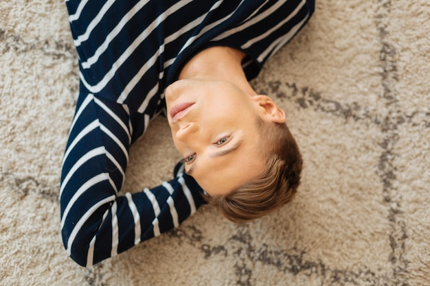 Train of thoughts. handsome thoughtful fair-haired well-built young man lying on the floor and thinking and looking in the distance