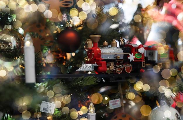 ぼやけた光でクリスマスの休日の木の飾りとしておもちゃを訓練する