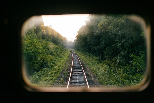 Путешествие на поезде. красивый далекий сценарный взгляд через окно от поезда катания на железной дороге с ladnscape природы на заходе солнца. туристическая поездка. атмосферный образ жизни. конец выходных. прощальный отпуск