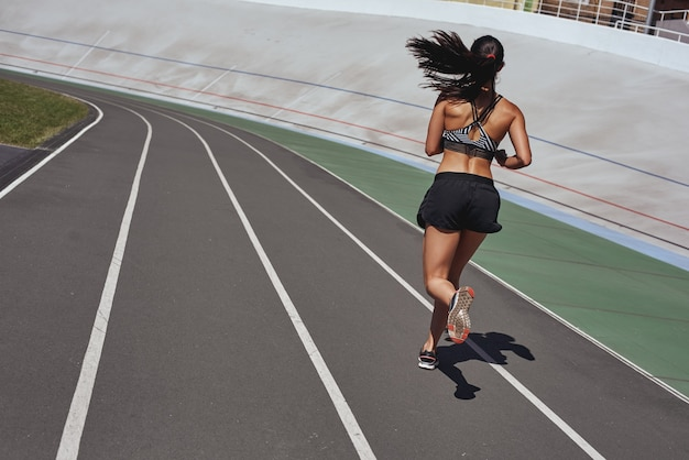 Train your body runner on the stadium track woman summer fitness workout jogging sport healthy