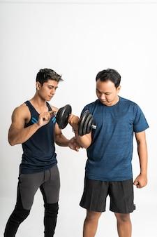 トレーナーは、上腕二頭筋のエクササイズのためにダンベルを持ち上げて、右手を動かすために手を握って男を伴います