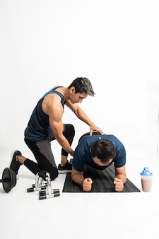 Trainer accompanies a man doing plank exercises holding back to make the right moves