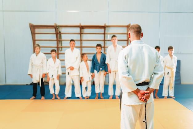 기모노를 입은 트레이너와 아이들, 어린이 유도 훈련. 체육관에서 젊은 전투기, 방어를위한 무술