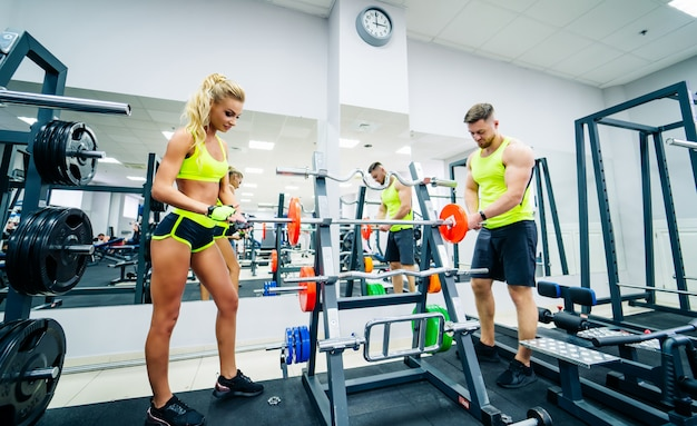 Тренер и клиент в тренажерном зале со спортивным оборудованием. молодой и подтянутый. концепция здорового образа жизни.
