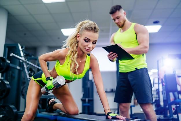 Тренер и клиент делает тренировки в тренажерном зале с гантелями. молодая блондинка с личным тренером по фитнесу. концепция фитнеса. крупный план. выборочный фокус.