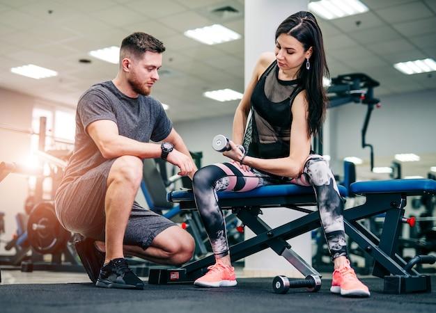 Тренер и клиент тренируются в тренажерном зале с гантелями