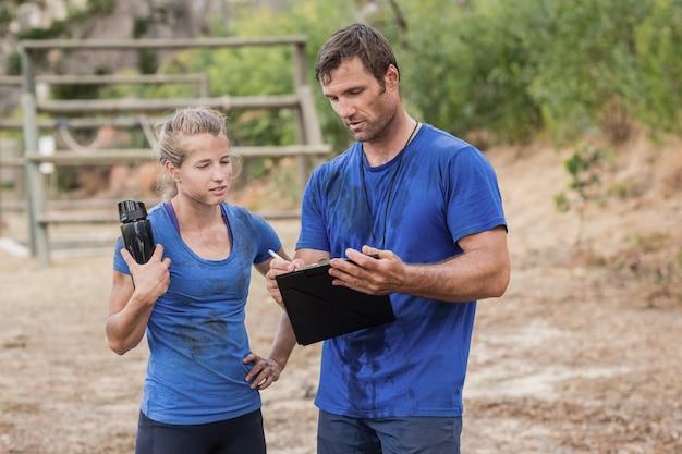 ブートキャンプの障害物競走中にクリップボードを介して議論するトレーナーと女性
