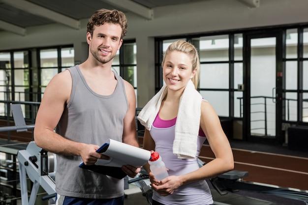 Тренер и женщина в тренажерном зале