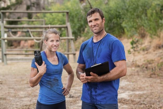 ブートキャンプの障害物競走中に一緒に立っているトレーナーと女性