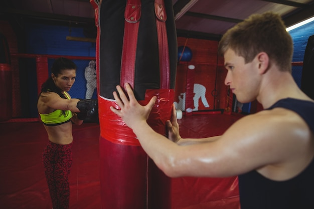 Trainer assisting a female boxer