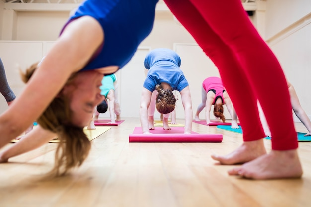 Trainer assisting group of people with downward dog yoga exercis