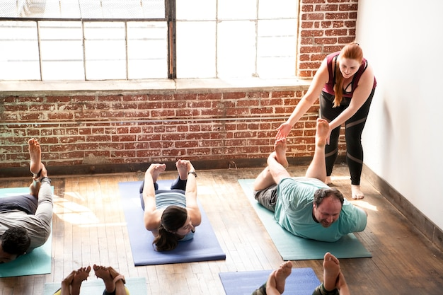 Trainer assisting her student doing a balasana pose