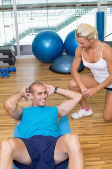 Trainer assisting man with abdominal crunches at fitness studio
