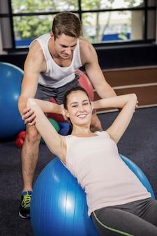 Trainer assisting a woman doing abdominal crunches on fitness ball
