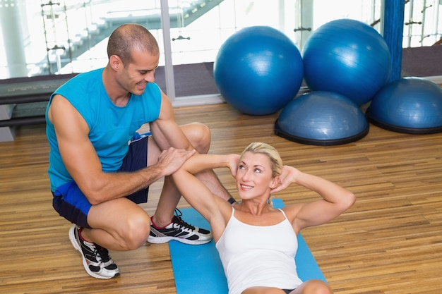 Trainer assisting woman with abdominal crunches at fitness studio