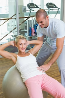 Trainer assisting woman with abdominal crunches at gym