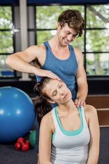 Trainer assisting woman with neck exercise