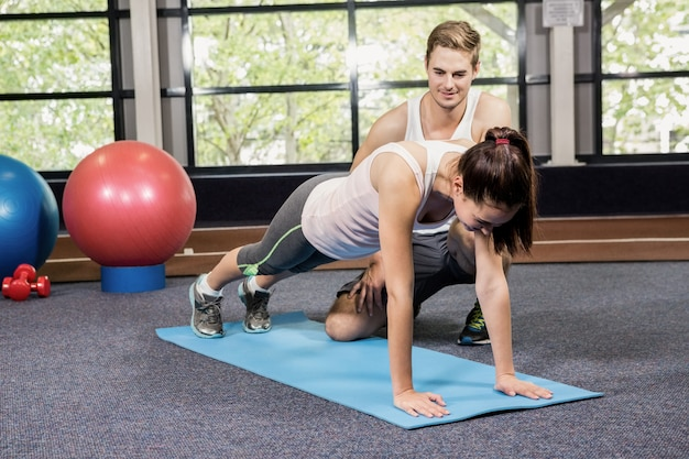 Trainer assisting woman with push ups