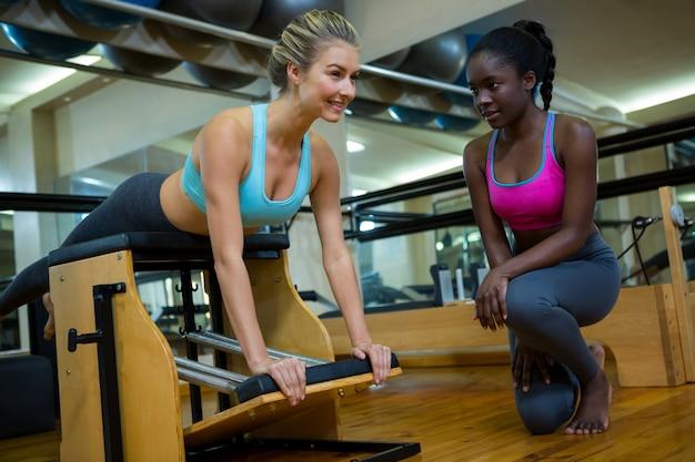 トレーナーのフィットネススタジオで二ンダ椅子を持つ女性を支援