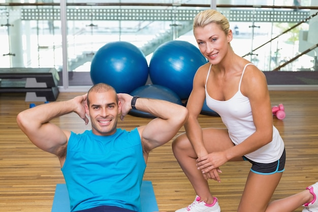 Trainer assisting young man with abdominal crunches at fitness studio