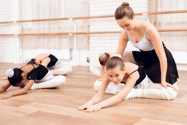 The trainer of the ballet school helps young ballerinas.