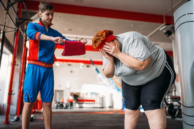 Trainer forces overweight woman to exercise, hard workout in gym.