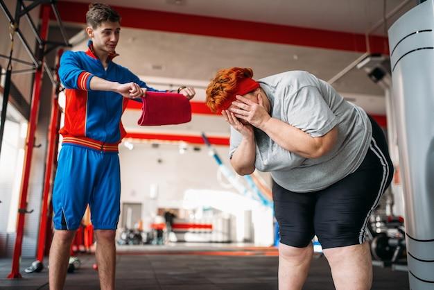 트레이너는 과체중 여성에게 운동을 강요하고 체육관에서 열심히 운동합니다.