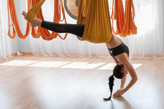 Девушка-тренер в тренажерном зале практикует флай-йогу в гамаке, балансируя и растягивая спину