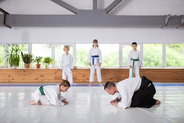 Trainer and girl preparing for fight studying martial arts