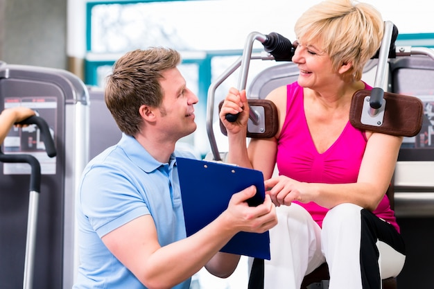 Trainer in gym assisting senior woman exercising