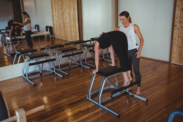 Тренер помогает женщине во время занятий пилатесом