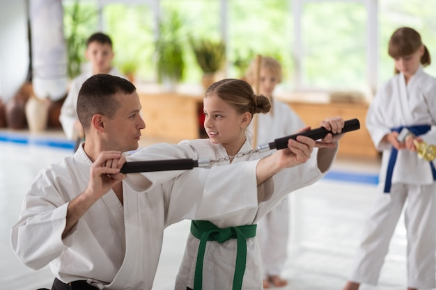 Trainer helping. dark-haired aikido trainer speaking and helping girl to use nunchucks