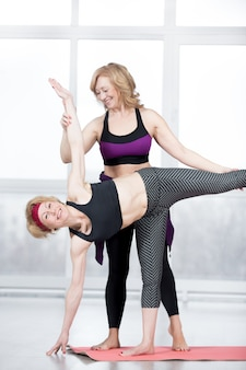 Trainer helping student to do ardha chandrasana pose