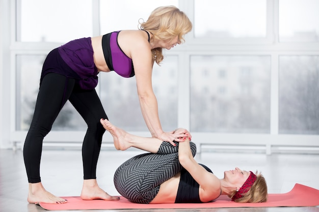 Trainer helping student to do knees to chest pose