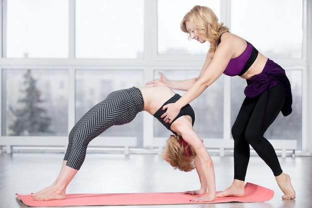 Тренер помогает студенту выполнять упражнения