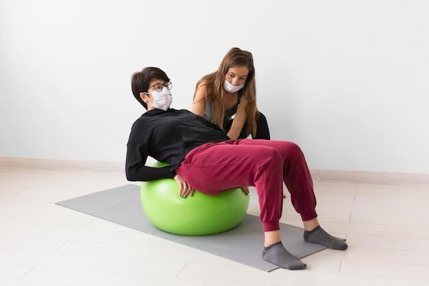 女性がフィットネスボールでコロナウイルスから回復するのを助けるトレーナー