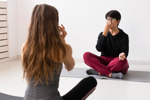 Тренер помогает женщине вылечиться от covid в помещении