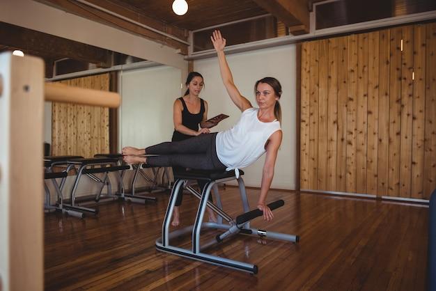 Trainer che aiuta una donna mentre pratica il pilates