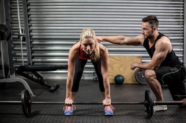 Trainer helping woman with lifting barbell at gym