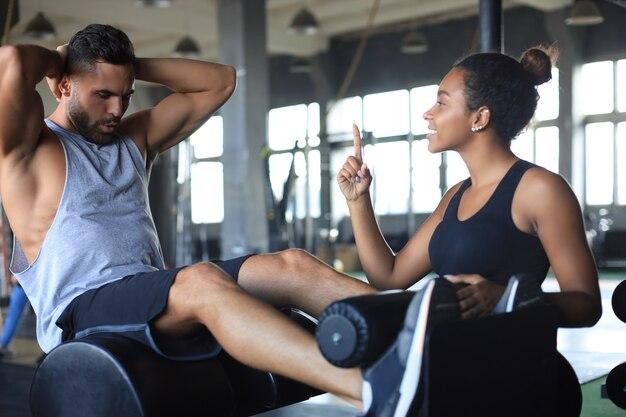 若い男がジムで腹筋運動をするのを助けるトレーナー。