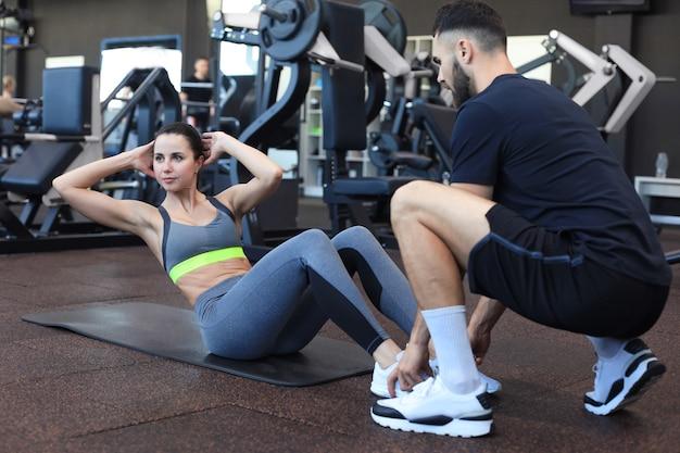 若い女性がジムで腹筋運動をするのを助けるトレーナー。