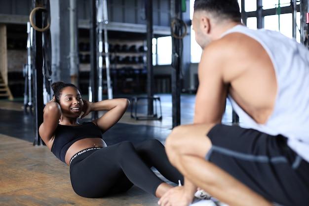 若い女性がジムで腹筋運動をするのを手伝うトレーナー。